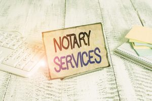 A notary services sign shown with keyboard and paper setting on a wooden table