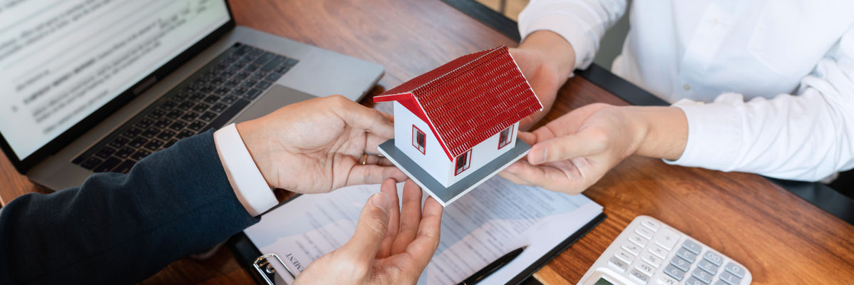 A small house model being held in the hands of two people while sitting at a desk