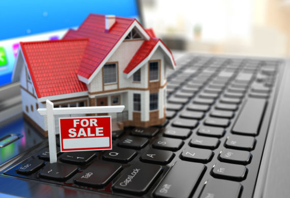 A Small toy model of a home and a for sale sign displayed on the keyboard of a laptop