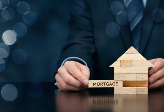 A small wooden house with the word mortgage displayed on a table by the hands of a man wearing a suit