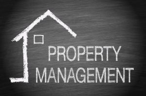 The words Property Management and a simple chalk drawn house displayed on a black chalkboard