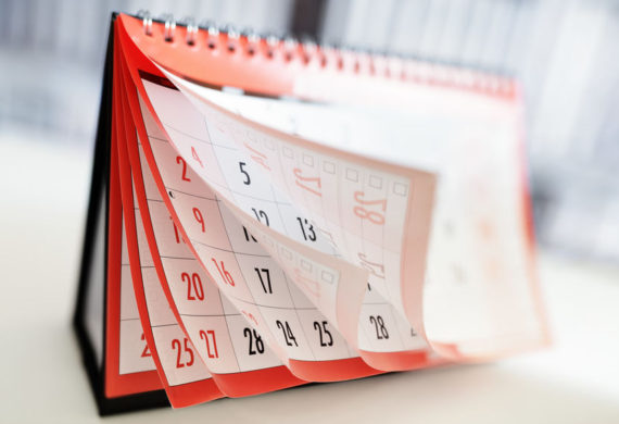 Desk calendar with pages curled and flipping up showing the months of pages