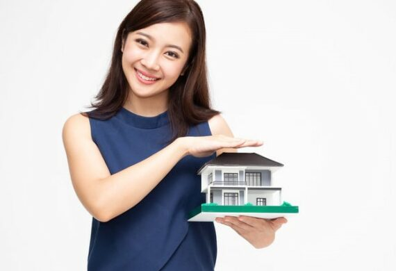 Pretty young Asian woman smiling and holding a small home model