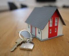 Small toy house and a key on a key ring displayed on a table